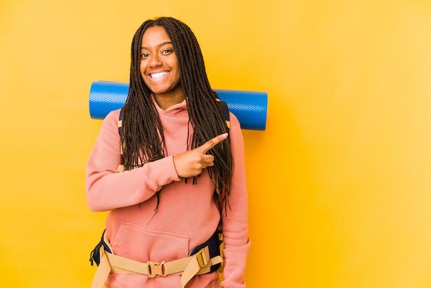 Junge afroamerikanische rucksacktouristin, die lächelt und beiseite zeigt und etwas an der leeren stelle zeigt.