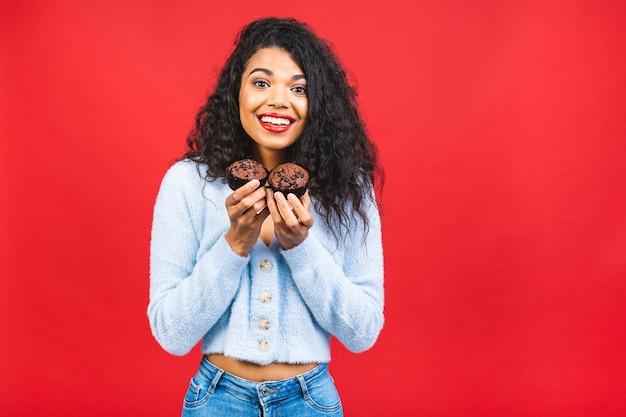 Junge afroamerikanische schwarze frau, die cupcakes lokalisiert über rotem hintergrund hält