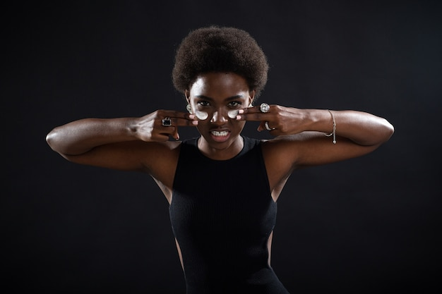 Junge afroamerikanische schwarze frau, die mit den fingern weißen cremeabstrich auf ihrem gesicht mit emotionen aufträgt