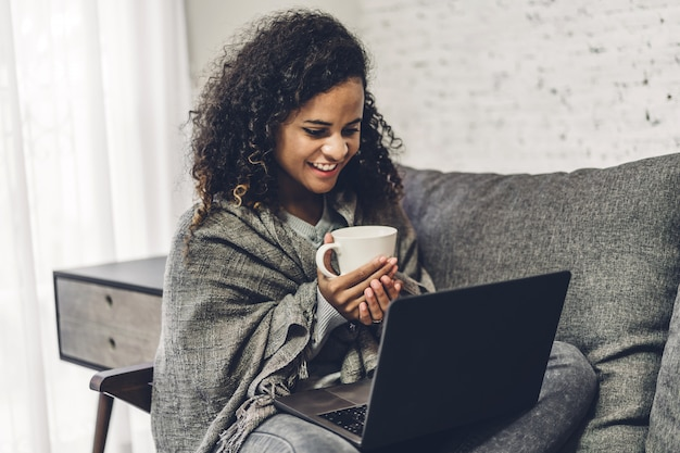Junge afroamerikanische schwarze frau, die sich entspannt und laptop-computer verwendet. frau, die soziale apps prüft und arbeitet. kommunikations- und technologiekonzept