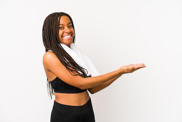 Junge afroamerikanische sportfrau isoliert, die einen kopienraum auf einer handfläche hält.