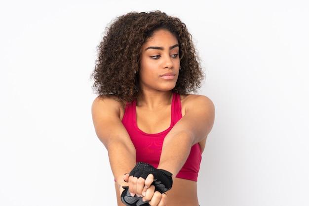 Junge afroamerikanische sportfrau lokalisiert auf weißem streckarm