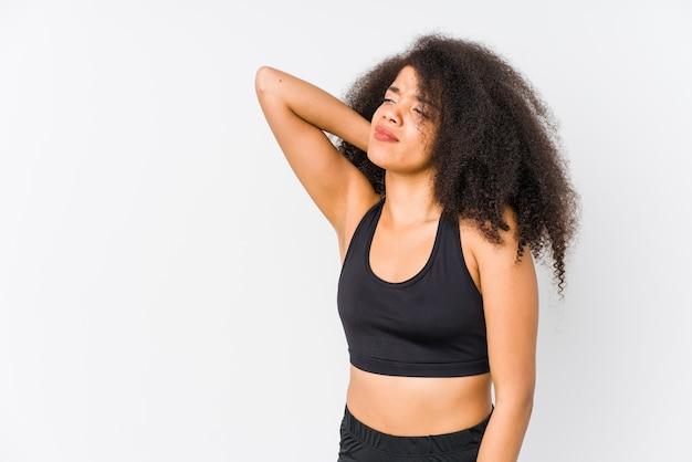 Junge afroamerikanische sportliche frau, die hinterkopf berührt, denkt und eine wahl trifft.