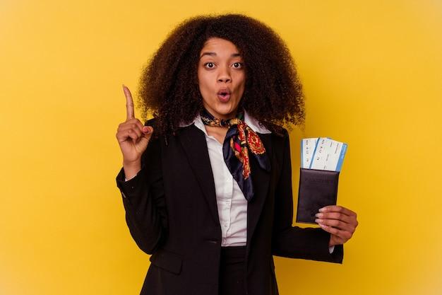 Junge afroamerikanische stewardess, die flugtickets einzeln auf gelb hält und eine großartige idee hat, konzept der kreativität.