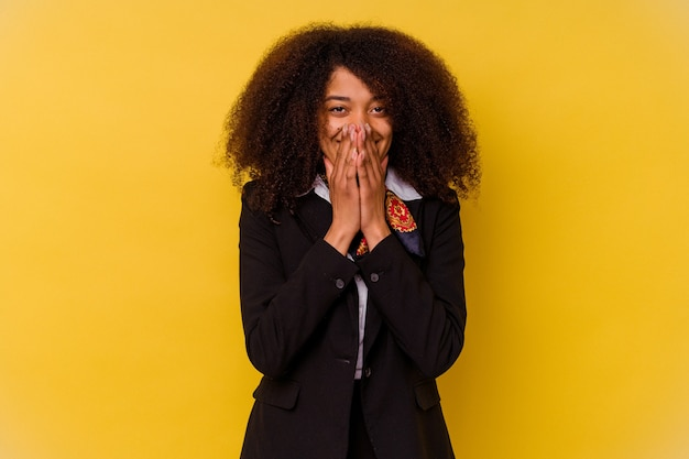 Junge afroamerikanische stewardess, isoliert auf gelb, lacht über etwas und bedeckt den mund mit den händen.