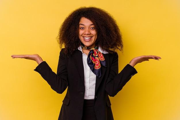 Junge afroamerikanische stewardess, isoliert auf gelb, macht mit armen eine waage, fühlt sich glücklich und selbstbewusst