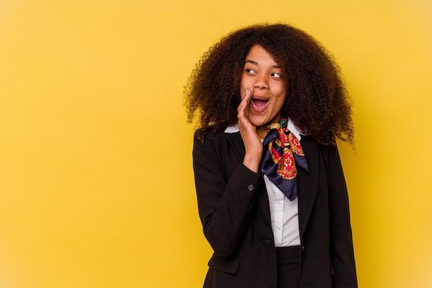 Junge afroamerikanische stewardess, isoliert auf gelb, sagt eine geheime heiße bremsnachricht und schaut beiseite
