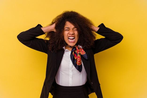 Junge afroamerikanische stewardess isoliert auf gelben ohren mit händen, die versuchen, nicht zu laut zu hören.