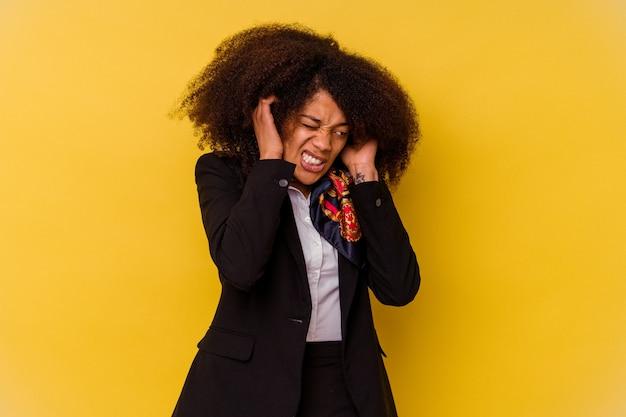 Junge afroamerikanische stewardess lokalisiert auf gelbem hintergrund, der ohren mit händen bedeckt.
