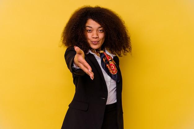 Junge afroamerikanische stewardess lokalisiert auf gelber streckender hand in der grußgeste.