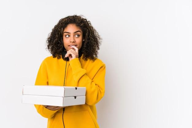 Junge afroamerikanische studentin, die pizzas hält, entspannte das denken über etwas, das einen kopienraum betrachtet.