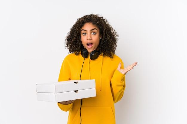 Junge afroamerikanische studentin, die pizzen hält, überrascht und schockiert.