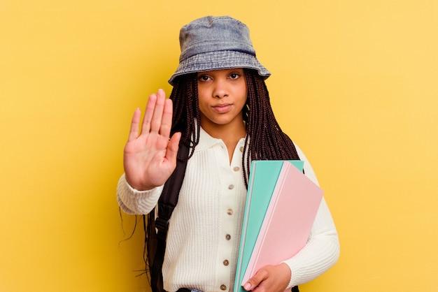 Junge afroamerikanische studentin lokalisiert auf gelbem hintergrund stehend mit ausgestreckter hand, die stoppschild zeigt, das sie verhindert.
