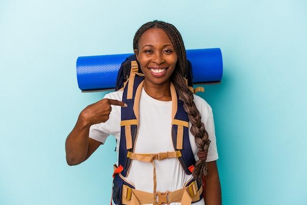 Junge afroamerikanische wandererfrau einzeln auf blauem hintergrund, die mit der hand auf einen hemdkopierraum zeigt, stolz und selbstbewusst