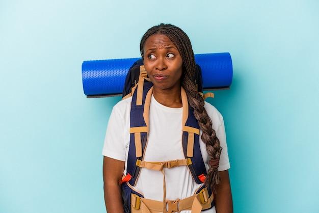 Junge afroamerikanische wandererin einzeln auf blauem hintergrund verwirrt, fühlt sich zweifelhaft und unsicher.