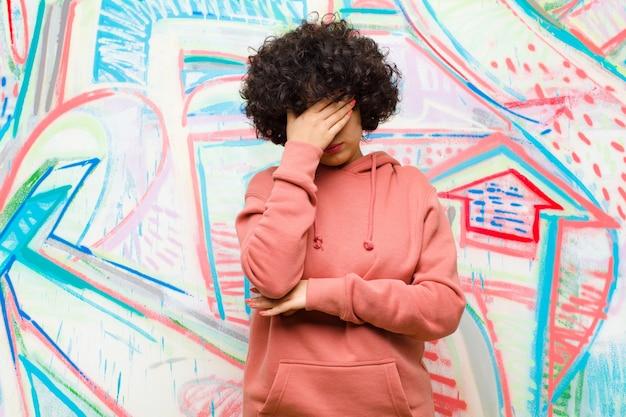 Junge afrofrau, die betont, beschämt oder, mit kopfschmerzen, gesicht mit der hand auf graffitiwand bedeckend gestört schaut