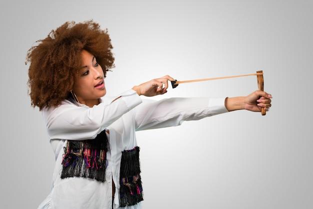 Junge afrofrau, die ein slingshot hält