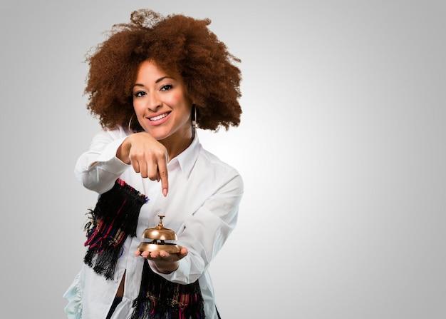 Junge afrofrau, die eine ringglocke hält