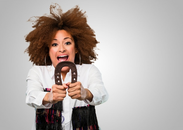 Junge afrofrau, die einen hrose schuh, glückkonzept hält