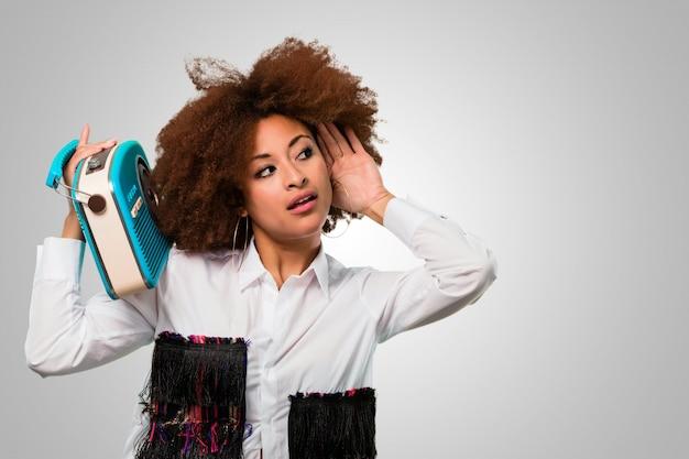Junge afrofrau, die einen weinleseradio hält