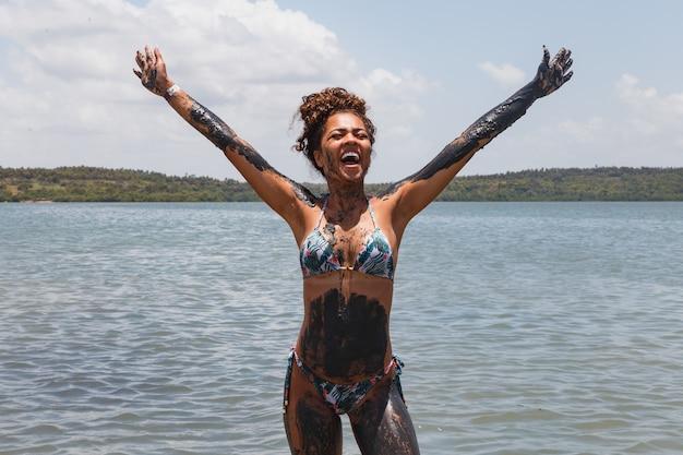 Junge afrofrau, die im natürlichen lehm im fluss badet.