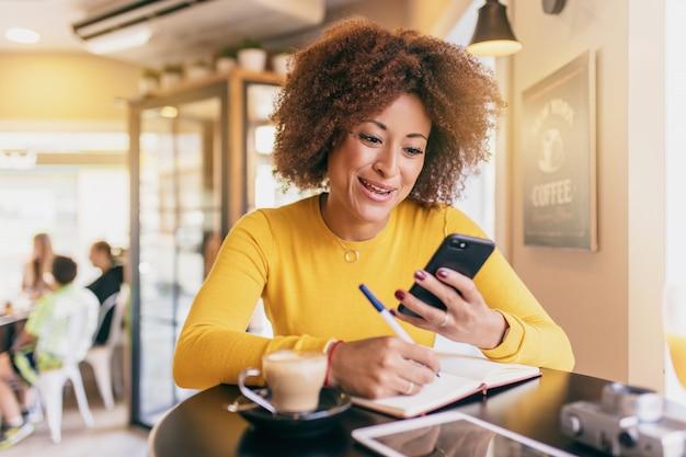 Junge afrofrau in einer kaffeestube, unter verwendung ihres handys und schreiben in ein notizbuch
