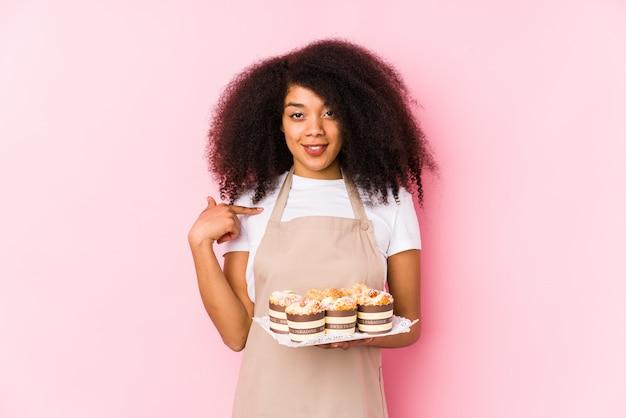 Junge afrogebäckherstellerfrau, die kleine kuchen lokalisiert hält junge afrobäckerfrauenperson, die eigenhändig auf einen hemdkopienraum, stolz und überzeugt zeigt