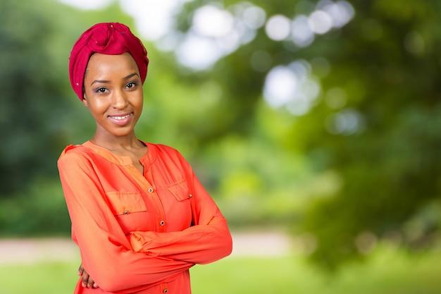 Junge afroschönheit, die ein rotes kopftuch trägt