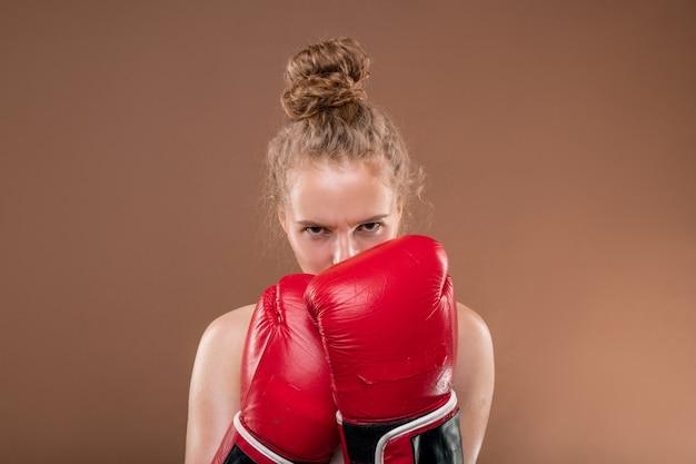 Junge aggressive sportlerin mit blondem lockigem haar, die hände in roten boxhandschuhen nahe ihrem gesicht hält, während sie sie vor dem kampf ansieht