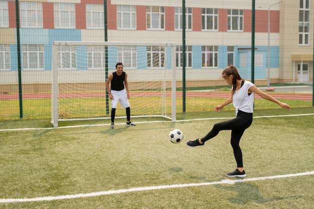 Junge aktive frau, die fußball gegen einen anderen spieler tritt, der durch netz am tor während des spiels auf dem feld steht