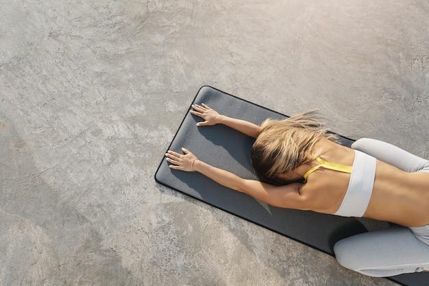 Junge aktive frau, die morgen yoga im freien inhaliert frische seeluft während sonnenaufgang kai trainingssitzung