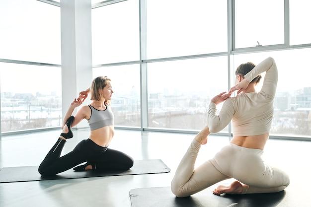 Junge aktive frau, die yoga-übung nach ihrem fitnesslehrer wiederholt, während beide auf matten während des trainings sitzen