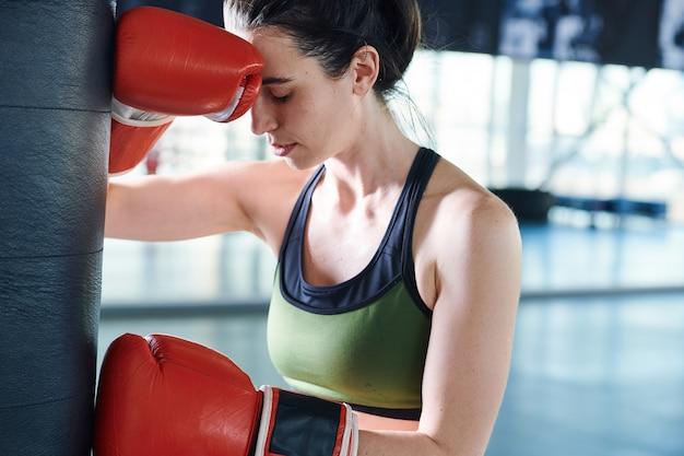 Junge aktive frau in boxhandschuhen und sportbekleidung, die kopfschmerzen oder probleme mit übungen haben