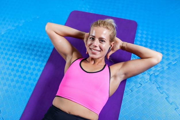Junge aktive frau mit schlankem körper, die sich nach bauchknirschen auf yogamatte im fitnesskurs entspannt. sportliche menschen, gesunder lebensstil