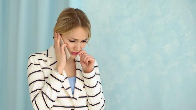 Junge alarmierte frau in einer gestreiften jacke, die am telefon spricht.