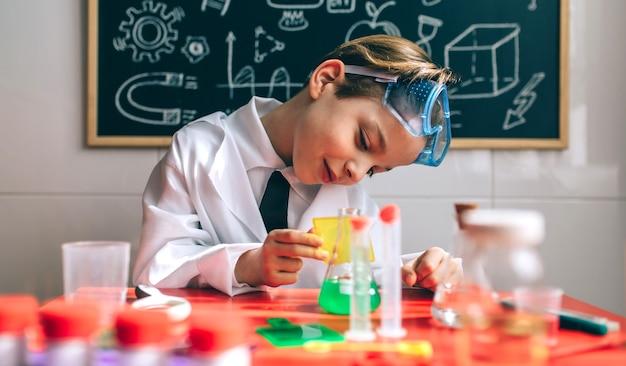 Junge als chemiker verkleidet, der mit einem chemiespiel vor einer tafel mit zeichnungen spielt