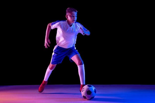 Junge als fußball- oder fußballspieler auf dunklem studio