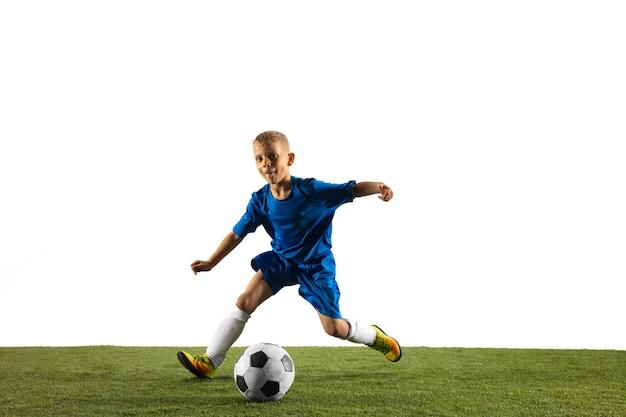 Junge als fußball- oder fußballspieler in sportbekleidung, der eine finte oder einen tritt mit dem ball für ein tor an der weißen wand macht.