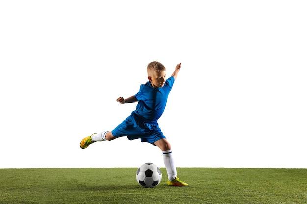 Junge als fußball- oder fußballspieler in sportbekleidung, der eine finte oder einen tritt mit dem ball für ein tor auf weißem studiohintergrund macht. fit spielender junge in aktion, bewegung, bewegung beim spiel.