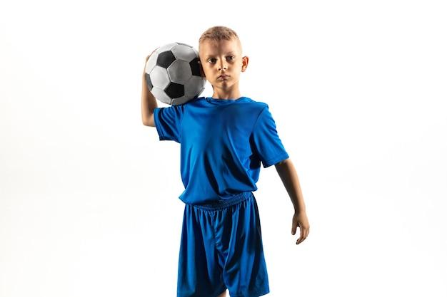 Junge als fußball- oder fußballspieler in sportbekleidung, der mit dem ball wie ein sieger steht