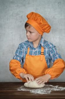 Junge als koch verkleidet ist mit dem kochen von hausgemachter pizza beschäftigt