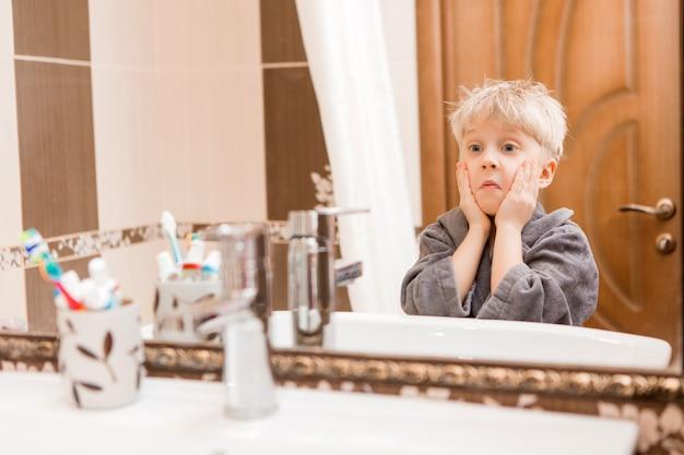 Junge am morgen seine zähne im badezimmer putzen
