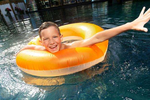 Junge am schwimmbad mit schwimmer