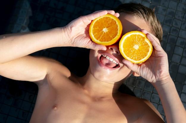 Junge am schwimmbad mit zitrusfrüchten