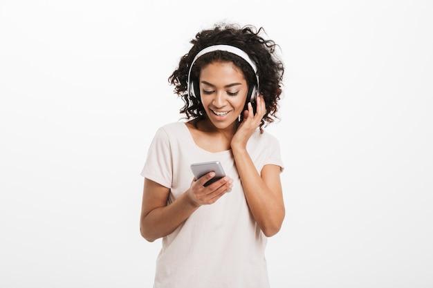 Junge amerikanische frau mit lockiger frisur, die musik hört und lieblingslied über drahtlose kopfhörer und smartphone genießt, lokalisiert über weißer wand