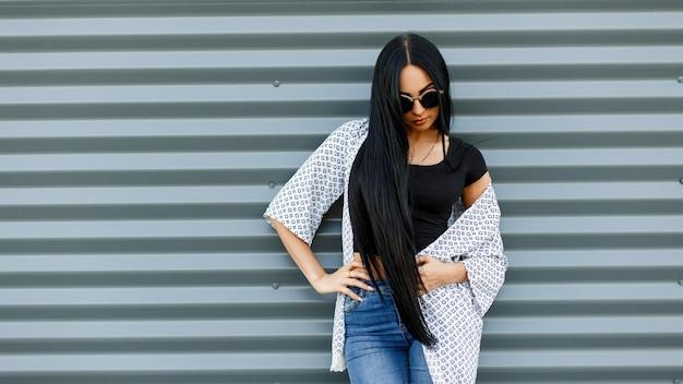 Junge amerikanische hipsterfrau mit langen haaren in runder sonnenbrille in einem schwarzen modischen oberteil in einer leichten sommerjacke in vintage-jeans steht nahe einer grauen metallwand