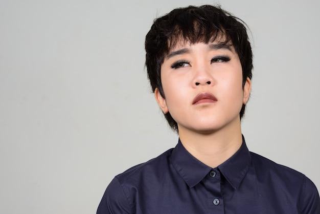 Junge androgyne asiatische transgenderfrau gegen weiße wand