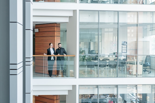 Junge angestellte des geschäftszentrums stehen am geländer und schauen sich um, innenraum des glasigen büroraums