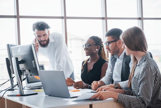 Junge angestellte, die im büro am tisch sitzen und einen laptop verwenden, ein teamarbeits-brainstorming-besprechungskonzept.