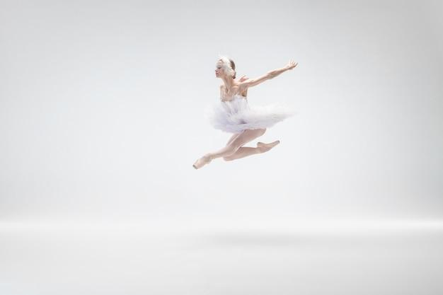 Junge anmutige ballerina auf weißem studiohintergrund